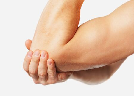 The man is touching the elbow due to acute pain. On a white background Reklamní fotografie