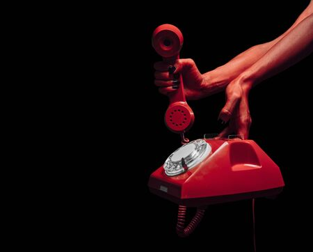 Red devil hands giving retro phone on dark background, space for text, Halloween or horror theme