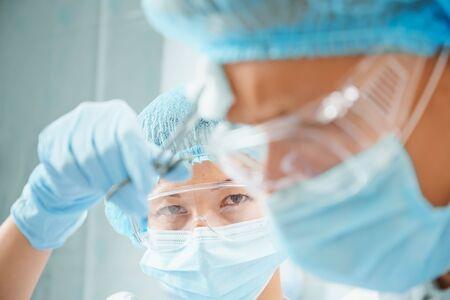Surgical woman nurse rubs forehead of man surgeon on operation, focus on nurse Reklamní fotografie