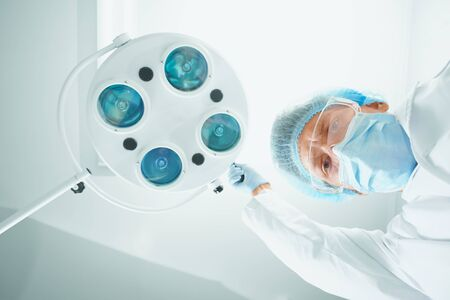 Man surgeon in protective uniform places a surgical lamp in operating room and looks at camera. Focus on Man surgeon