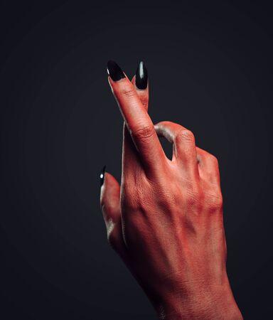 Red demon or devil hand with gesture cross fingers on dark background. Halloweenhorror theme