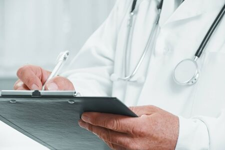 Unrecognizable senior man physician writes medical records on clipboard