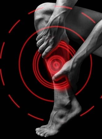 Acute pain in the male calf muscle, black and white image, pain area of red color Stock Photo - 128532106