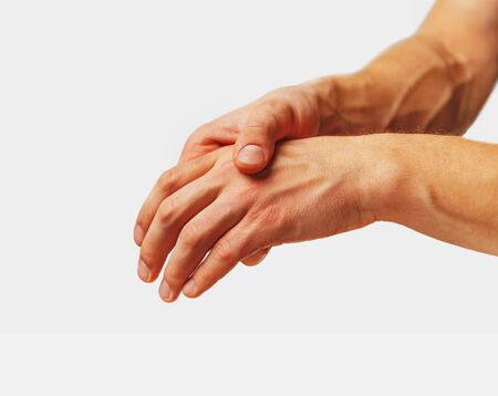 Pain in a male hand. Man holds his hand.