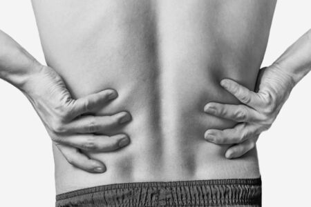 Acute pain in a male lower back. Monochrome image, isolated on a white background