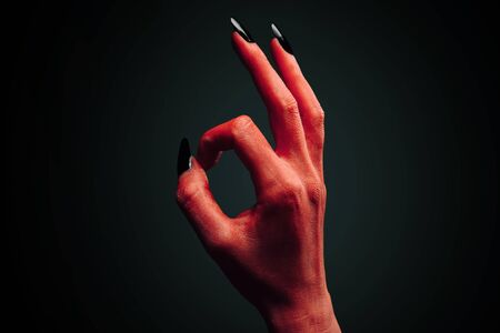 Red demon or devil hand with gesture OK on dark background. Halloweenhorror theme