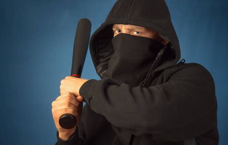 Dangerous hooligan with baseball bat ready for fight