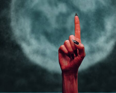 Red devil hand with gesture pointing upward on background of full moon, space for text. Halloween or horror theme