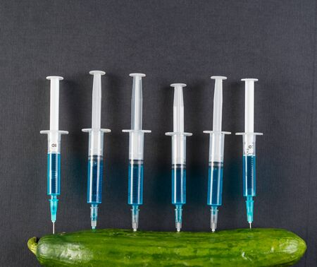 Blue liquid in the syringe injected into cucumber, space for text