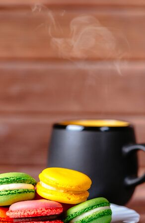 Colorful macarons cookies and cup of hot drink on a wooden background.