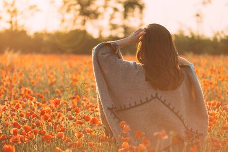 Unrecognizable woman wearing in poncho walking in red poppies flowers meadow at sunset outdoor, rear view.