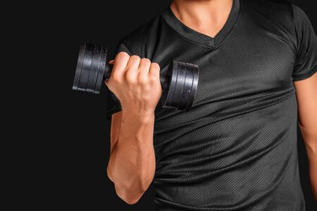 Unrecognizable man exercises with metal dumbbell Stock Photo