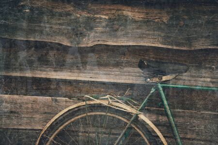 Wheel and seat detail of old bicycle on wooden background, textured vintage image Reklamní fotografie
