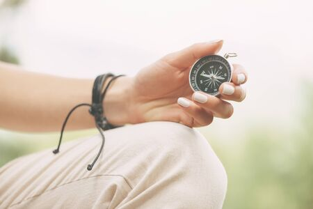 Female hand with magnetic compass outdoor.