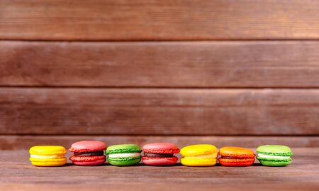 Colorful sweet macarons dessert in a row on wooden table. Copy-space in upper part of image.