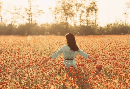 Beautiful girl walking through poppy field and touching flowers, summer vacations. 写真素材