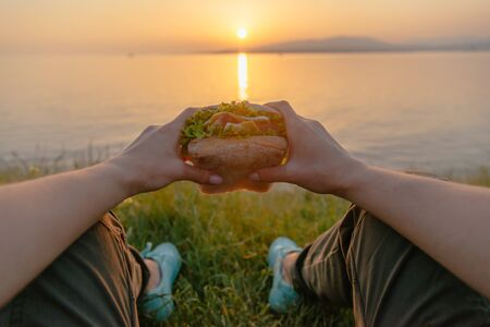 Woman resting by the sea with fresh tasty burger and enjoying view of summer sunset, point of view.