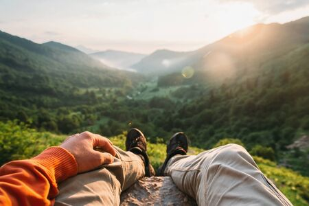 Hiker young man sitting in summer mountains at sunset, point of view shot