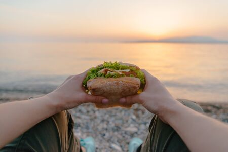 Young woman holding fresh tasty fast food burger sandwich and resting by the sea at summer sunset, point of view.
