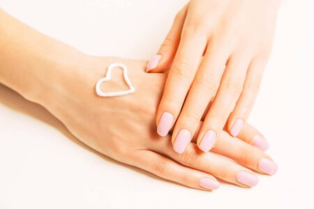 Moisturizing cream in shape of heart on a female hand, concept of skincare and beauty. 스톡 콘텐츠