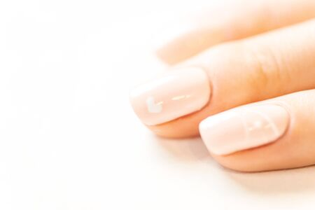 Female fingers with professional manicure and natural beige color polish, close-up.