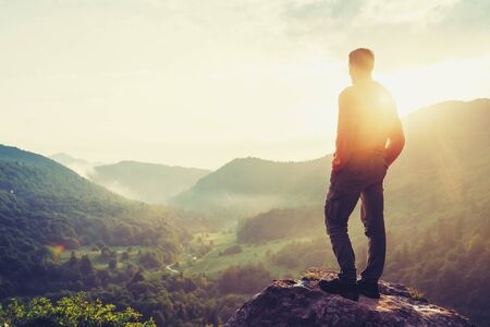 Traveler young man standing in the summer mountains at sunset and enjoying view of nature.