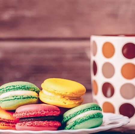 Sweet macaroons dessert of different colors on a plate near the cup.