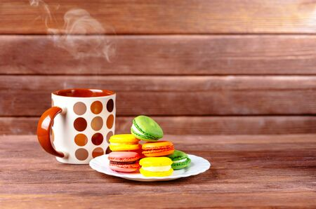 Sweet colorful macarons dessert on a plate and cup of hot beverage on wooden background.