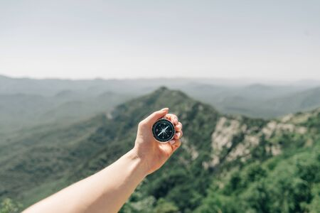 Female hand with magnetic compass high on background of summer mountain ridge, point of view.
