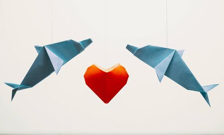 Two origami dolphin around red paper heart on white background. Greeting card for Valentines day.