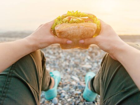 Young woman holding and ready to eat fresh fast food burger sandwich while resting on nature outdoor, point of view.