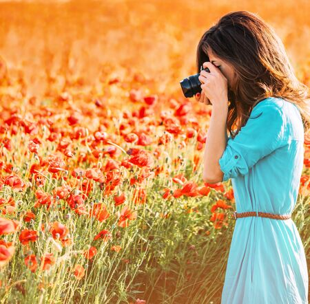 Photographer young woman taking photographs with camera the poppies meadow on sunny day. 写真素材