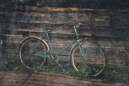 Old-fashioned bicycle on background of wooden house outdoor. Image with retro textured effect Reklamní fotografie
