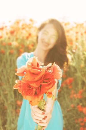Smiling beautiful young woman giving a bouquet of red poppies in summer, focus on flowers.