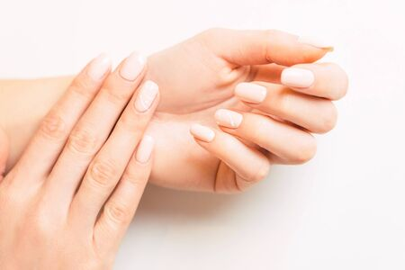 Beautiful young female hands with stylish professional manicure, nails of pastel natural color. Concept of beauty salon.