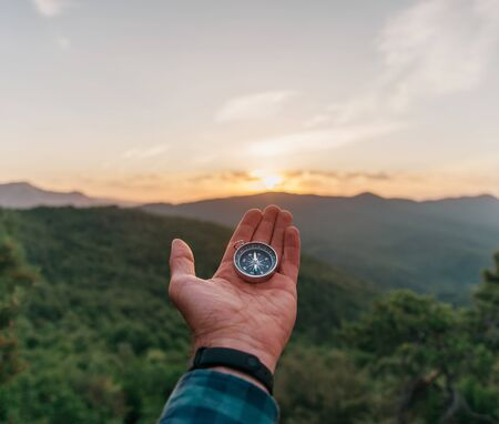 Magnetic compass on male palm hand in summer mountains at sunrise outdoor, point of view. Concept of travel and nature explore.