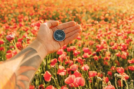 Man's hand with travel compass on background of red poppies meadow, point of view.