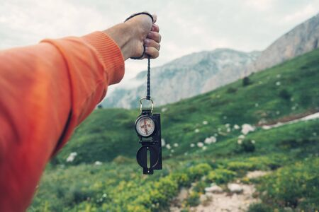 Explorer young man searching direction with a compass in summer mountains. Point of view shot Imagens