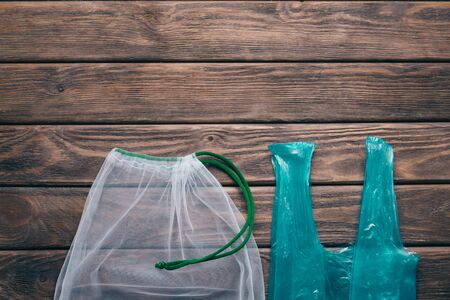 Reusable mesh eco bag vs plastic package on a wooden background. Zero waste concept.