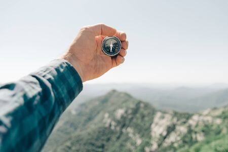 Explorer young man holding compass in hand in front of summer mountain ridge, point of view. Concept of hiking and travel.