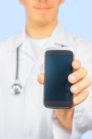 Smiling man doctor is showing mobile phone screen, copy-space Stock Photo