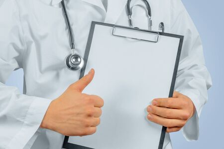 Unrecognizable man doctor shows gesture thumb up in front of clipboard, space for text Imagens