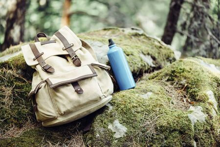 Backpack with water bottle on nature outdoor, hiking equipment.