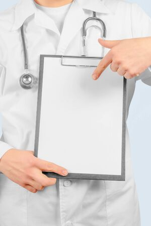 Unrecognizable man physician is pointing on blank clipboard, space for text