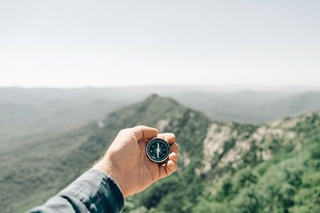 Male hand with magnetic compass high in summer mountains, point of view. Concept of travel and hiking.