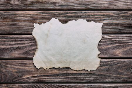 Old blank paper with burned edges on wooden background, top view. Free space for text.