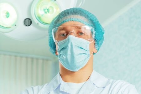Portrait of man physician surgeon in an operating room on background of surgical lamp Stock Photo