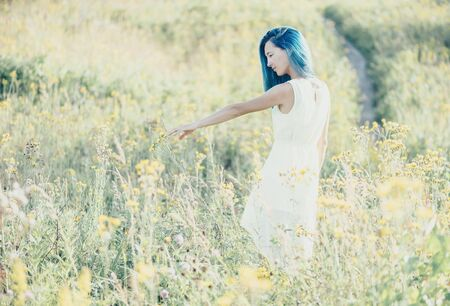 Beautiful young woman walking on wildflower meadow in summer.