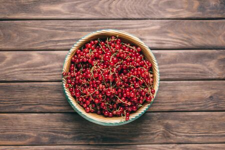 Fresh ripe red currant in a bowl on a wooden background, top view.