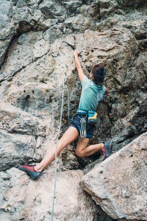 Sportliche junge Frau im Sicherheitsgurt mit Ausrüstung, die die Felswand im Freien klettert